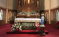 Mary, crowned in May, stands in front of the altar.